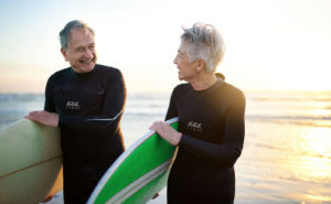 senior couple surfing at the beach