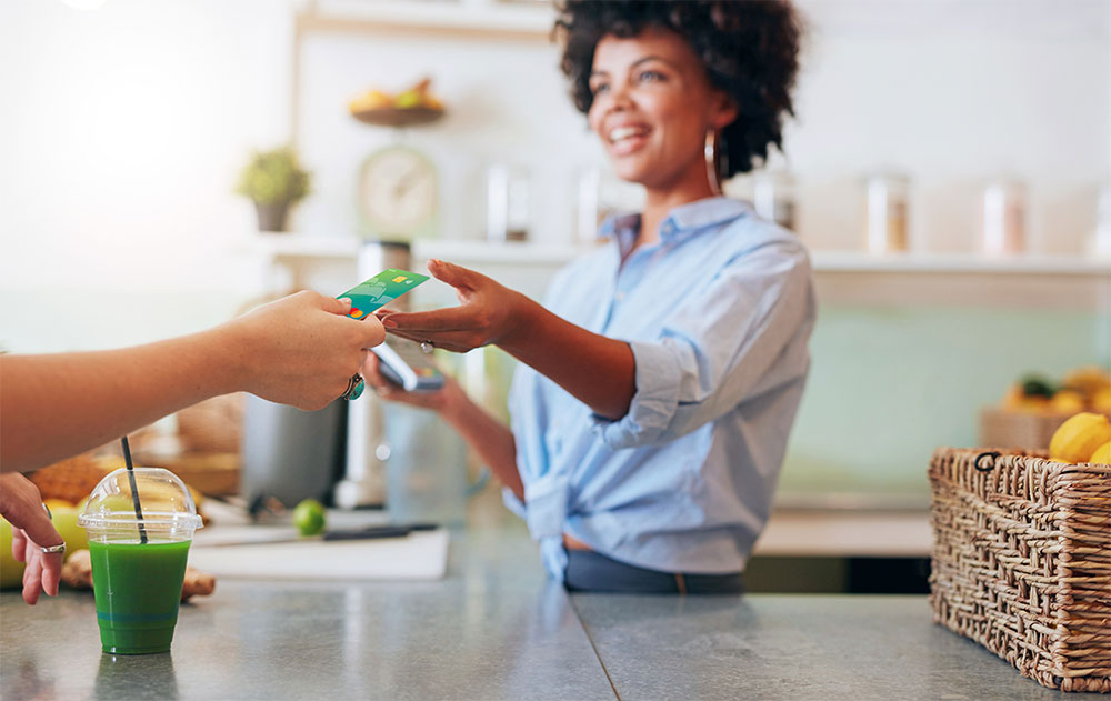 woman handing debit card to cashier